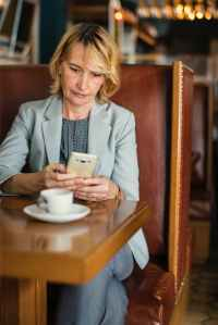 woman in grey notched lapel suit jacket holding smartphone sitting beside wooden table